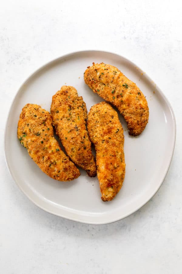 Round grey plate of cooked crispy chicken tenders
