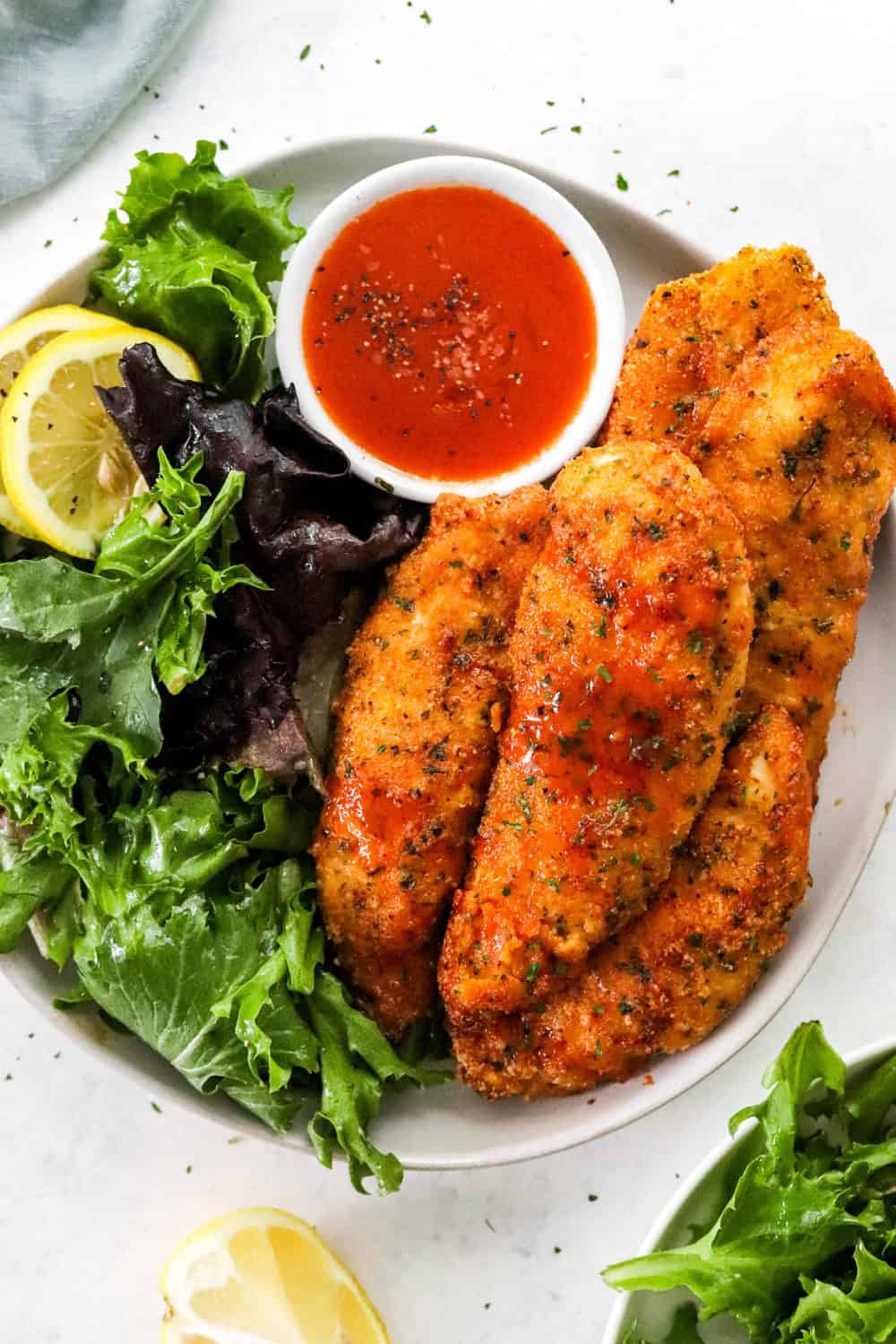 Crispy breaded chicken tenders on a round white plate with a mixed green salad and a bowl fo red sauce next tot it.
