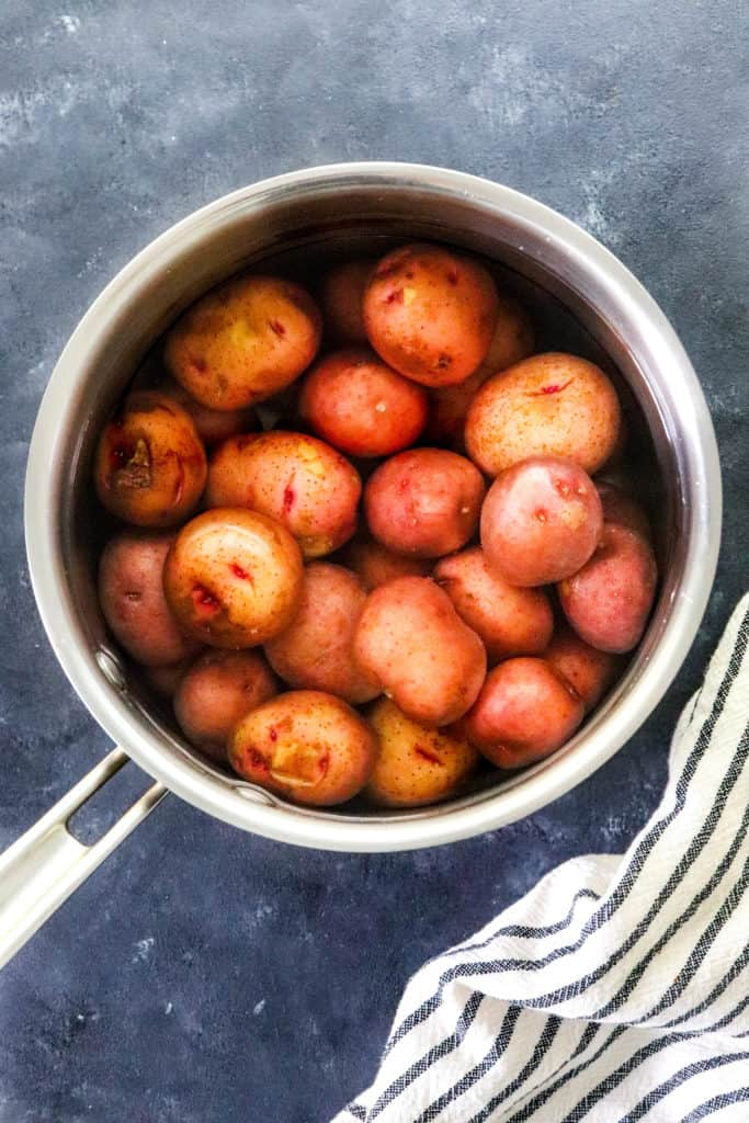 Silver pot filled with red potatoes covered in water on a blue surface with a striped towel in front of it.