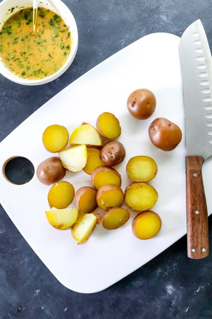 white cutting board with sliced red potatoes  and a brown handled knife on ti with a bowl of dressing in back of it
