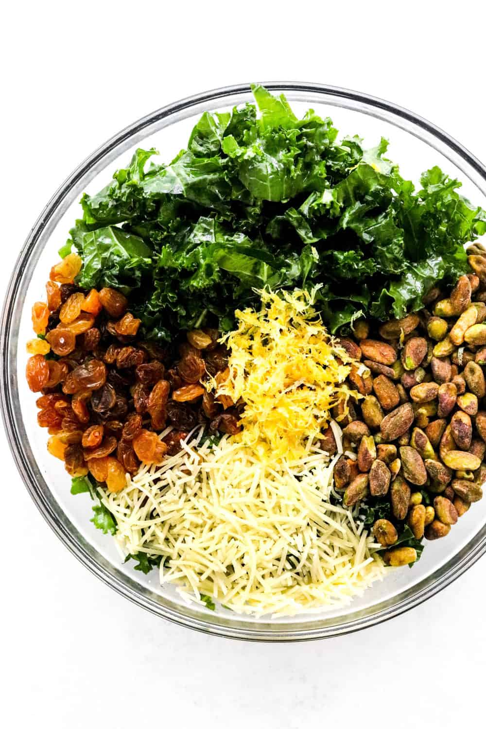 Chopped kale, pistachios, gold raisins, lemon zest and shredded parmesan cheese separated in a large round glass bowl on a white surface