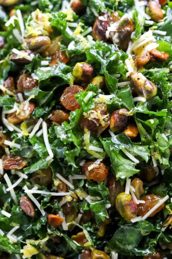 Close up of chopped dark green kale mixed in with golden raisins, pistachios, lemon zest and shredded cheese