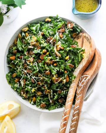 round white bowl of kale salad topped with nuts, raisins and shredded cheese with wooden salad spoons in the side of he bowl
