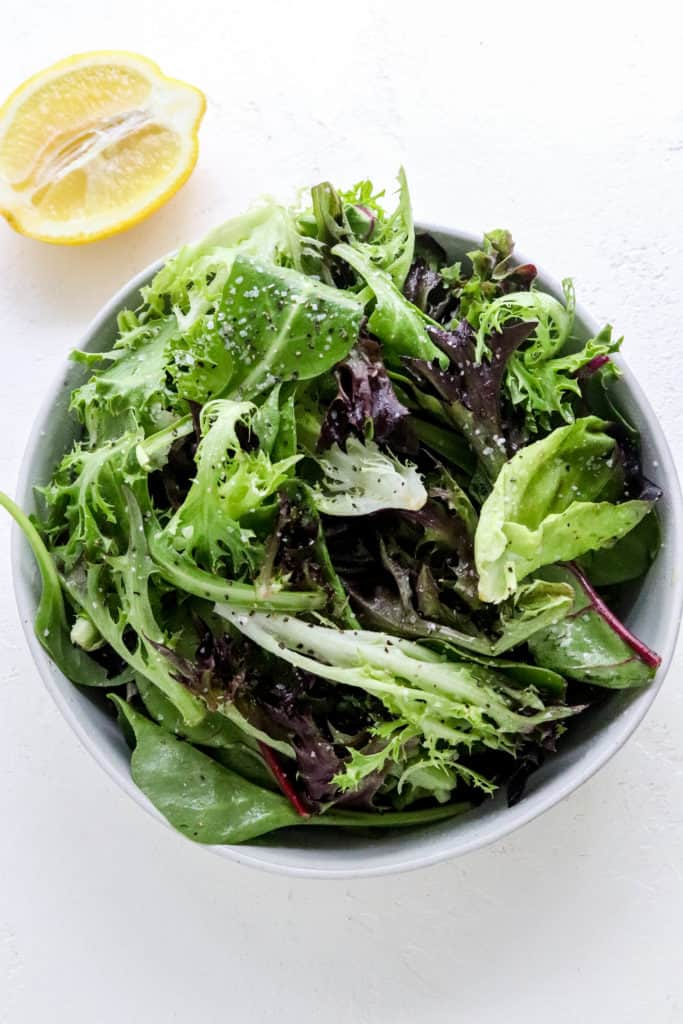 White bowl filled with mixed greens with half of a sliced lemon behind it