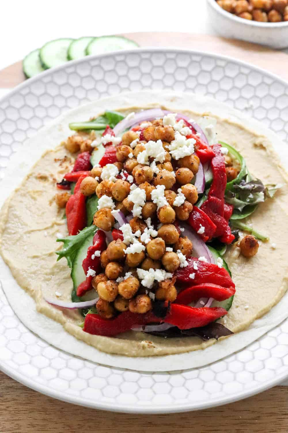 Close up of a pile of chickpeas and red bell peppers, greens and cheese on top of hummus spread over a flour tortilla on a white textured plate with sliced cucumber and a bowl of chickpeas behind it.