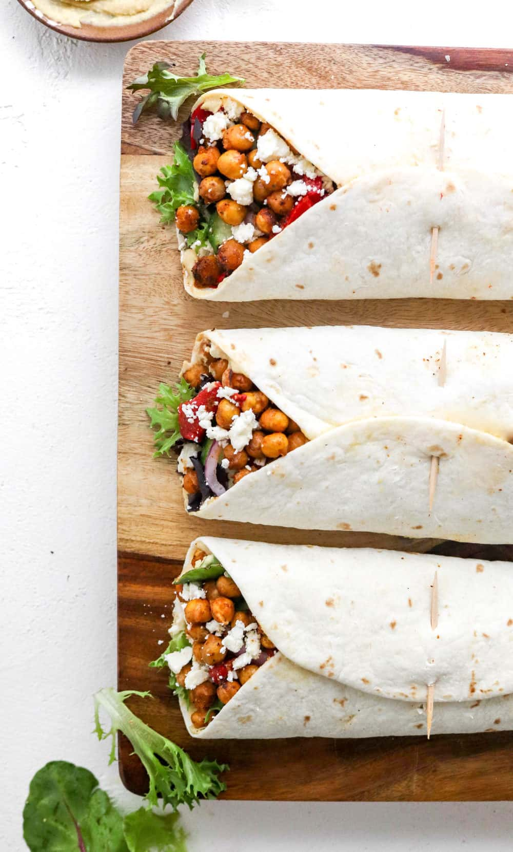 Three tortilla hummus wraps filled with crispy chickpeas and veggies on top of a wooden cutting board on a white surface.