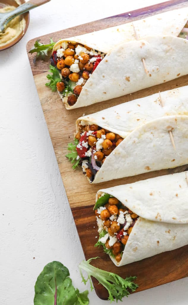 A wooden board topped with three wrapped white flour tortillas filled with crispy roasted chickpeas and veggies and topped with crumble white cheese with a bowl of hummus behind it.