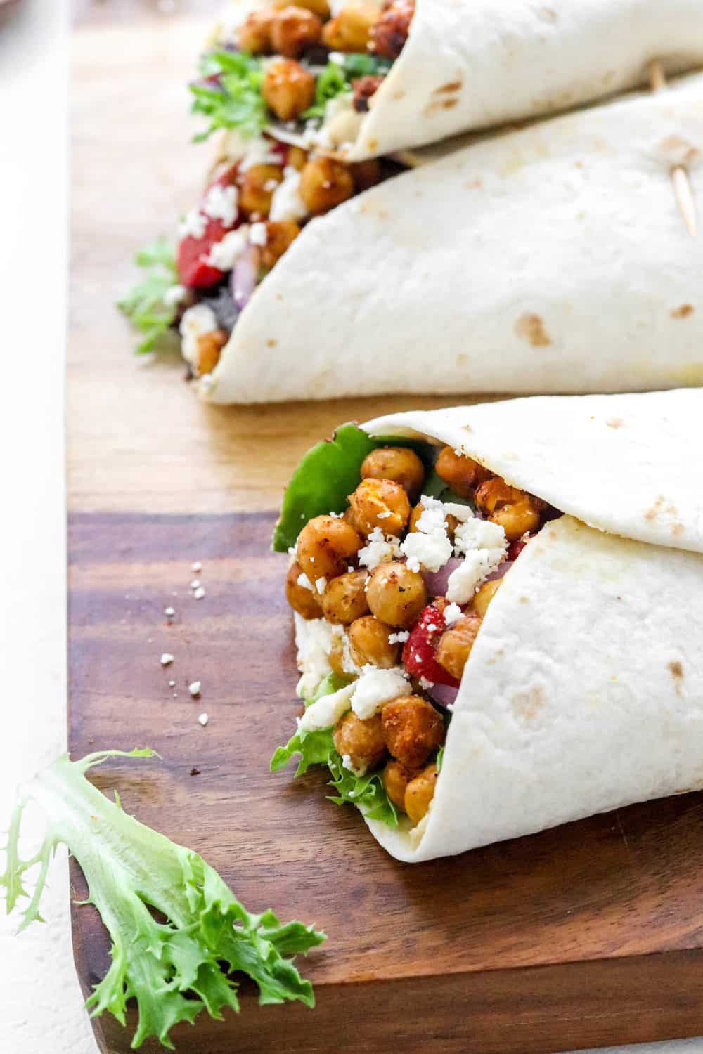 Close up of the end of a flour tortilla wrap folded and filled with crispy chickpeas, feta cheese, Lettuce and peppers on a wooden surface with a pice of lettuce in from to it and more wraps behind it.