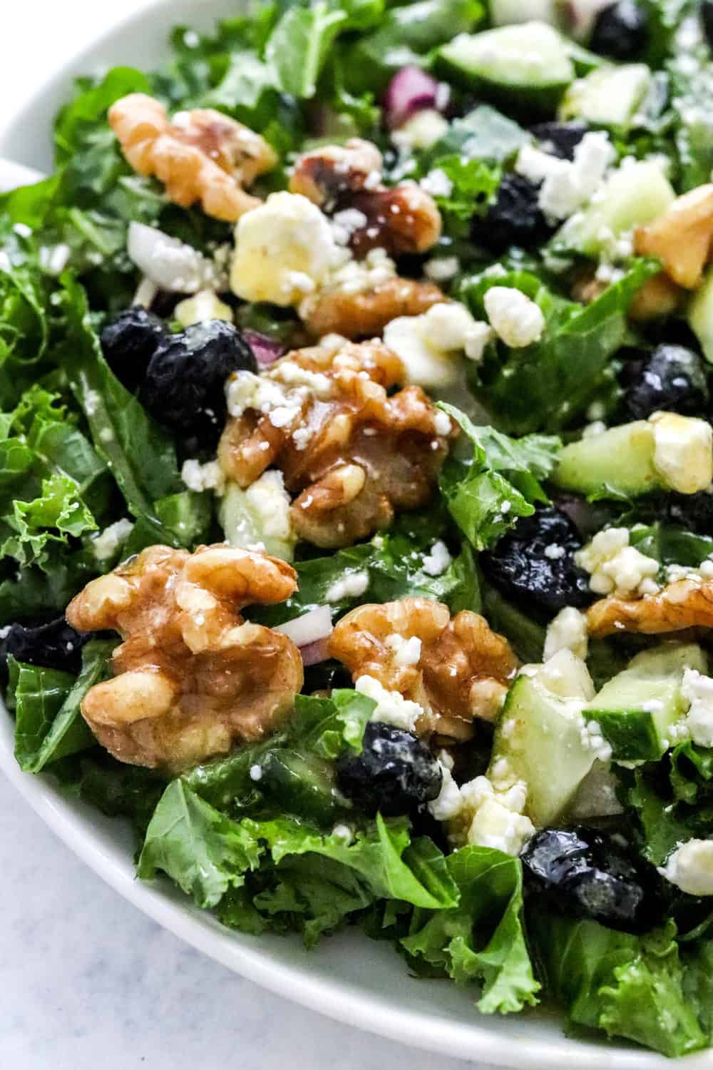 Close up of chopped kale salad with creamy dressing on it with walnut and berries on the salad.