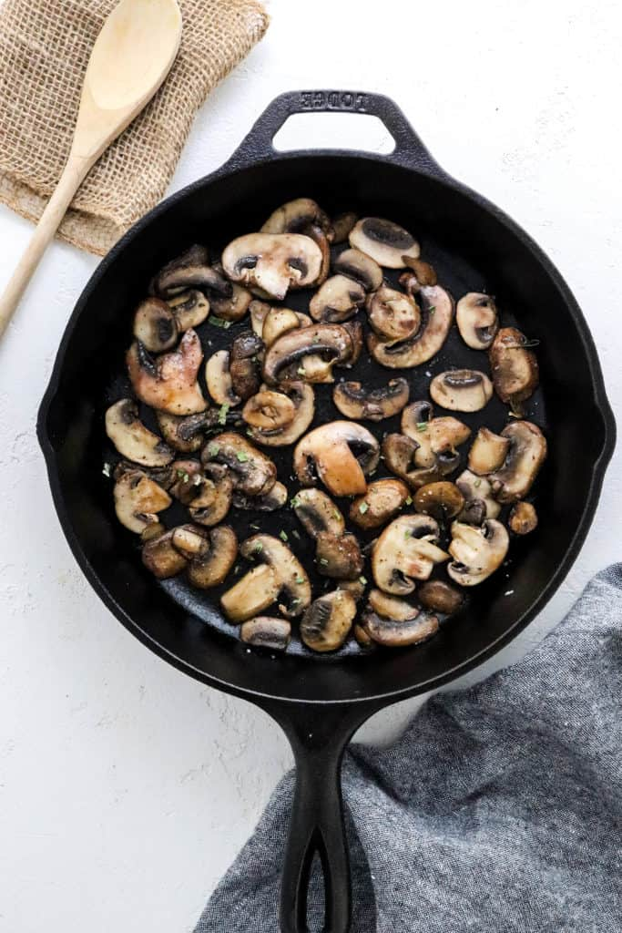 Cast iron pan filled with sliced cooked mushrooms with a wooden spoon behind it and a grey cloth in front of it.