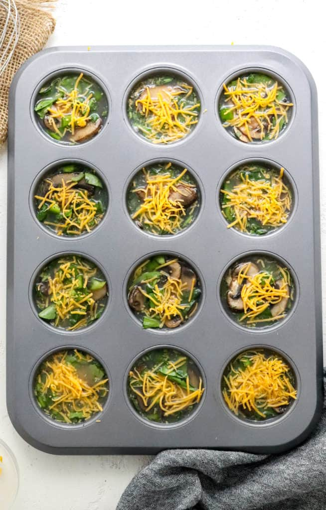Uncooked veggie egg white muffins in a grey muffin tin