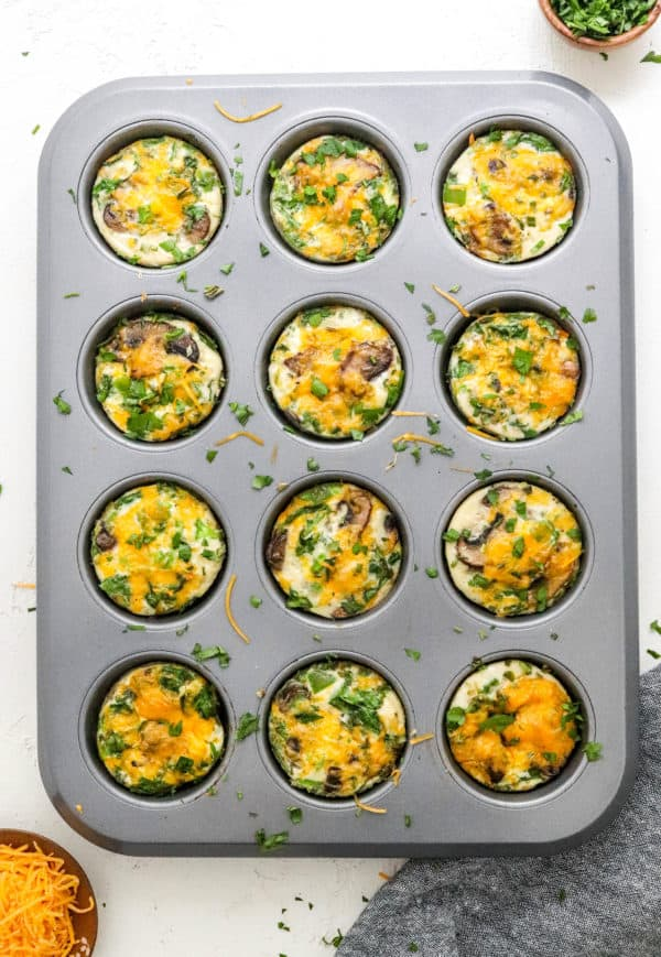 Baked egg white muffins with green and yellow in them in a grey muffin pan with herbs sprinkled on top of them