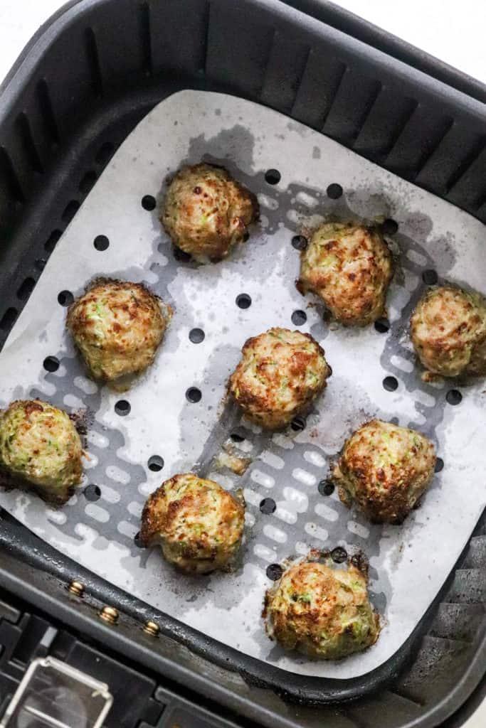 Cooked turkey meatballs in an air fryer basket