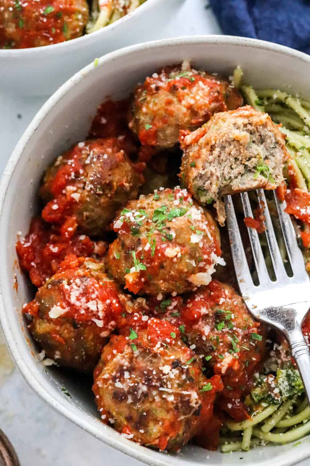 Round grey bowl filled with meatballs covered in red sauce with a meatball on a fork in the bowl over spaghetti