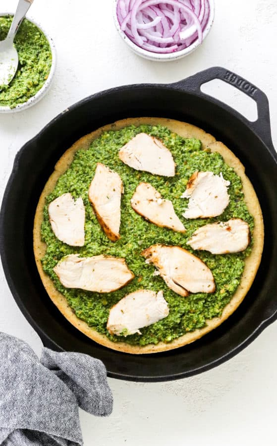 Chicken and pesto layered onto a pizza crust in a cast iron pan