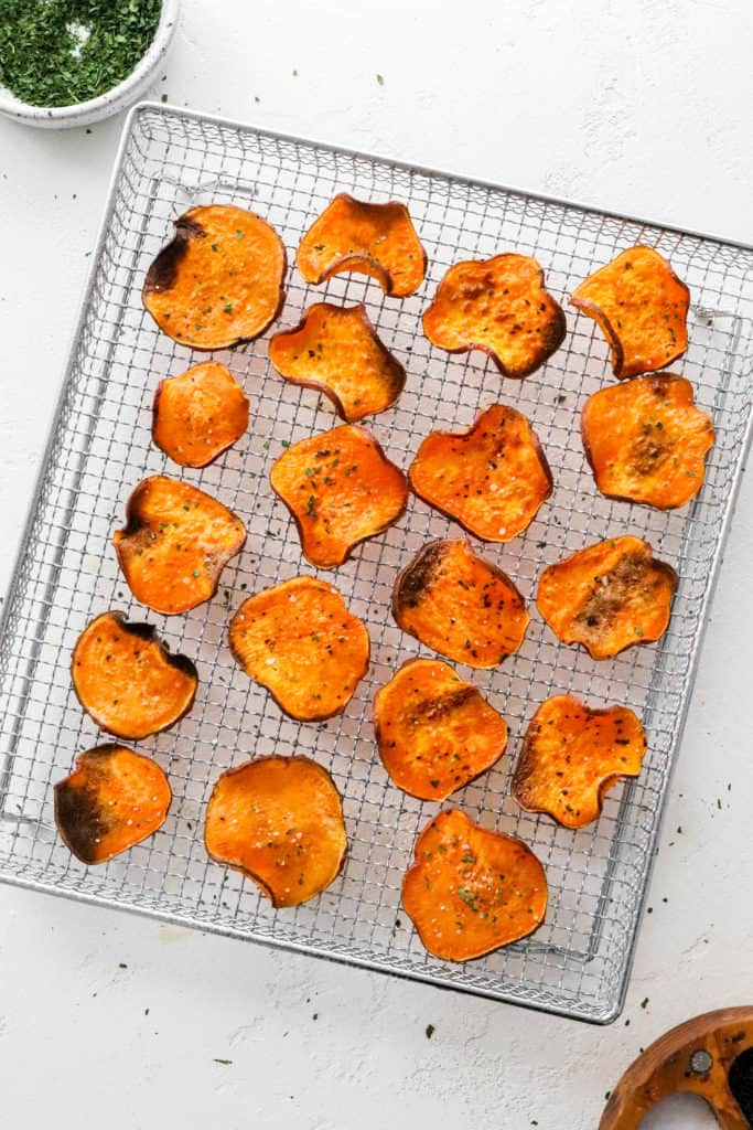 Crispy baked sweet potato chips laid out on a metal basket