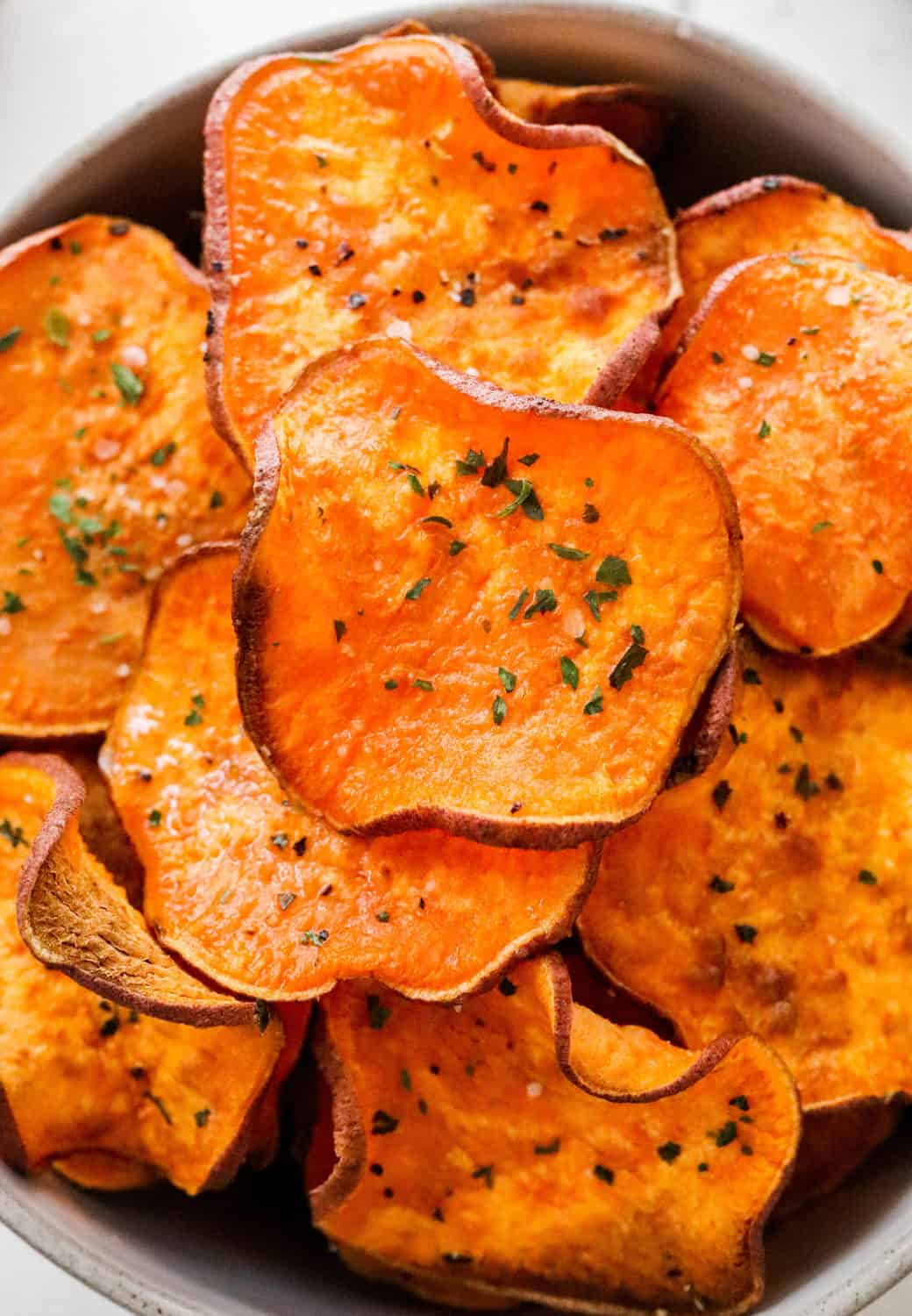 Round sweet potato chips with pepper and parsley on them
