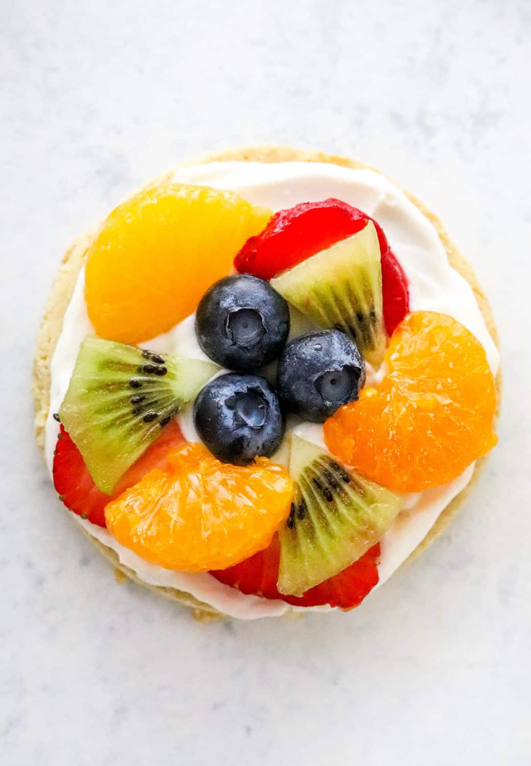 Single fruit pizza cookie on a white surface with blueberries, sliced strawberries, oranges and sliced kiwi on top of it.