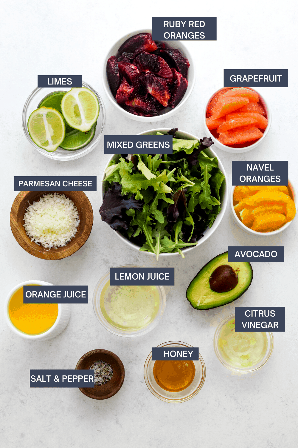 Bow of mixed greens with bowls of segmented oranges and grapefruit around it with shredded parmesan in a bowl, orange juice, bowl of lemon juice, sliced half of an avocado, honey and salt and pepper in front of it.