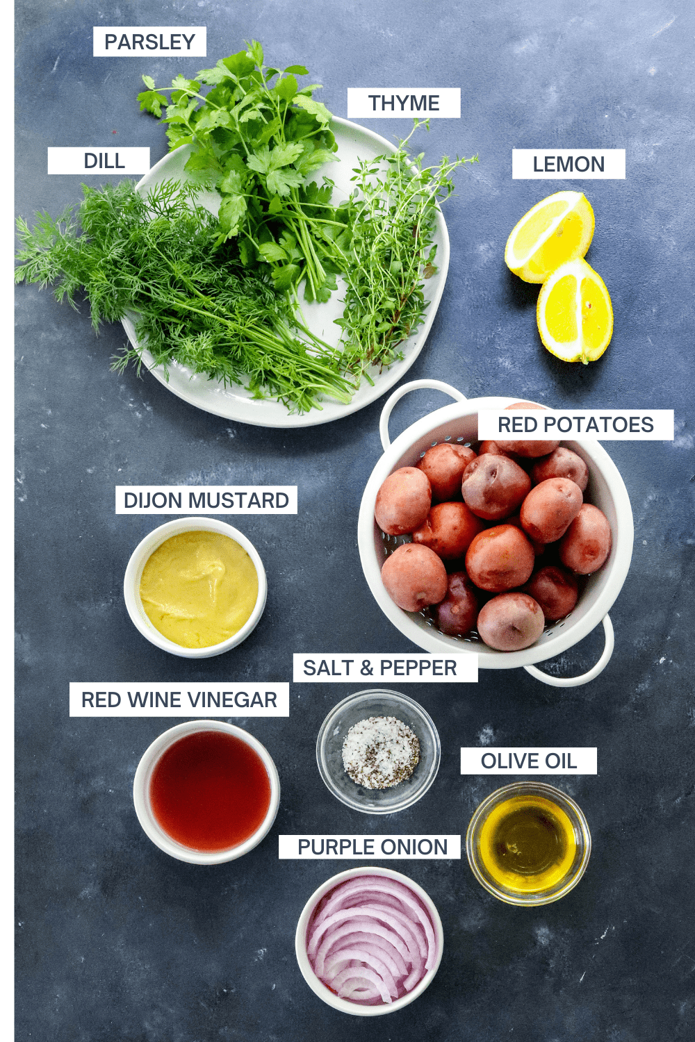 Green herbs on a round plate, sliced lemon, white bowl of whole rd potatoes, bowl of dijon mustard, bowl of olive oil, bowl of sliced rd onion and a bowl of red wine vinegar on a blue surface with labels of the ingredients over each item.