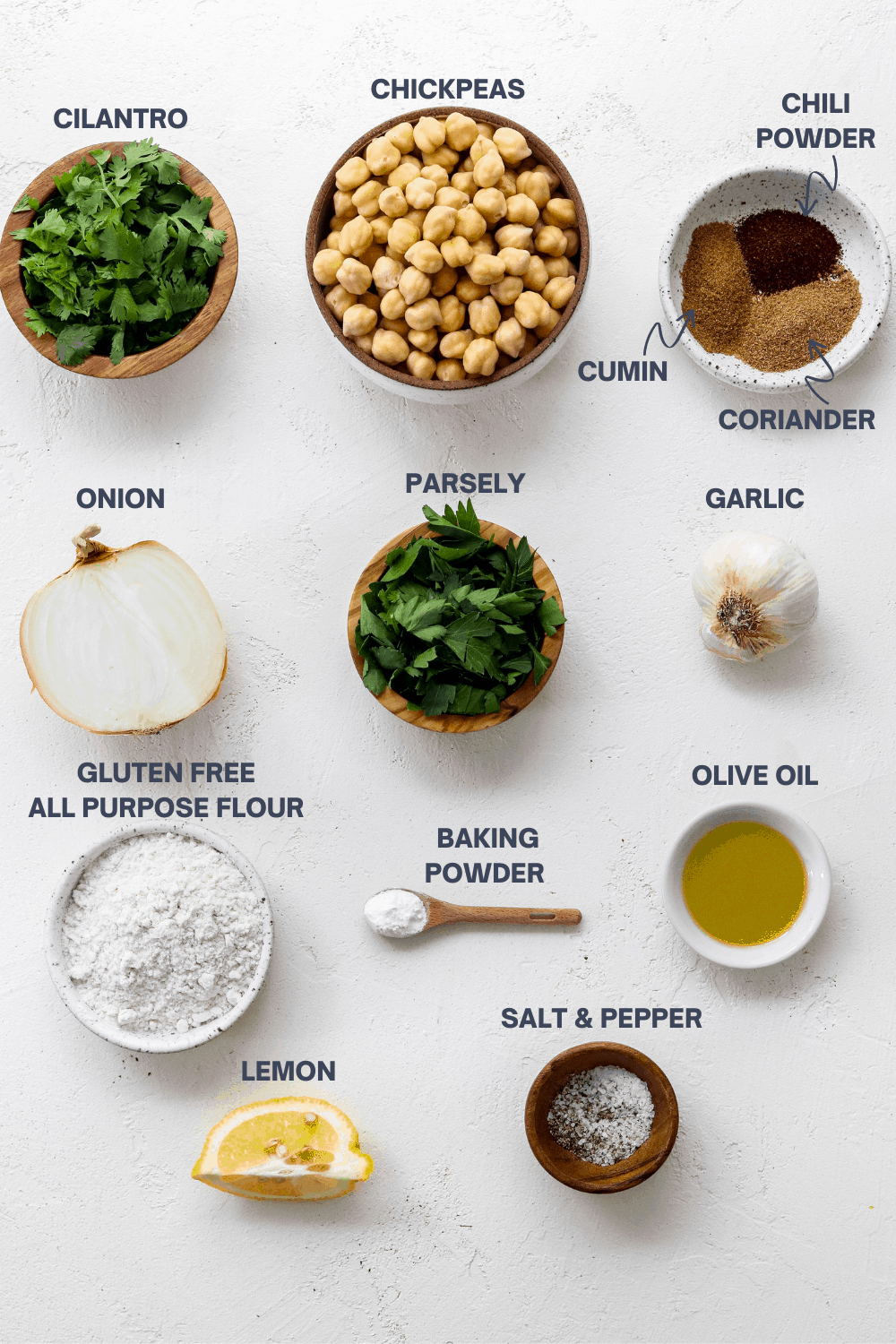 Bowl of chopped cilantro next to a bowl of chickpea with a bowl of spices next to it, a sliced onion, bowl of parsley, bulb of garlic, bowl of olive oil, bowl of flour, wooden spoon with baking powder and a slice of lemon in front of it.