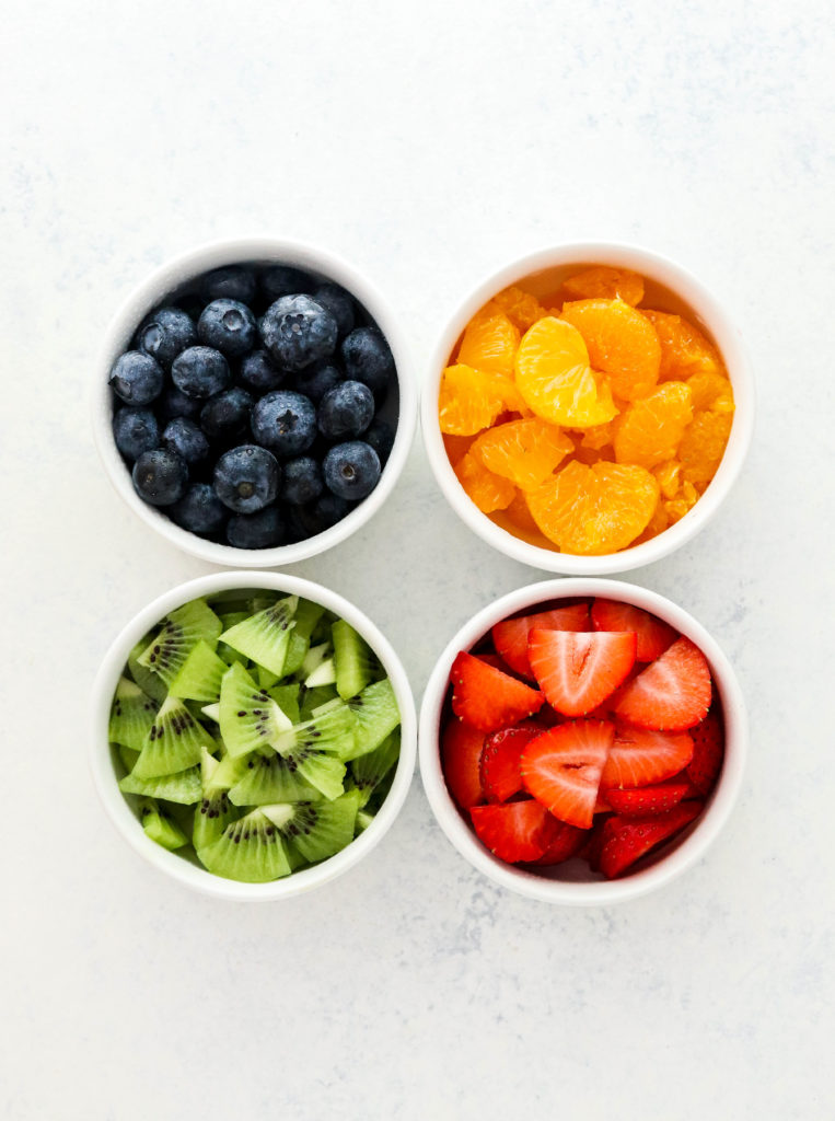 4 small white bowls filled with blueberries, oranges, cut kiwi and sliced strawberries