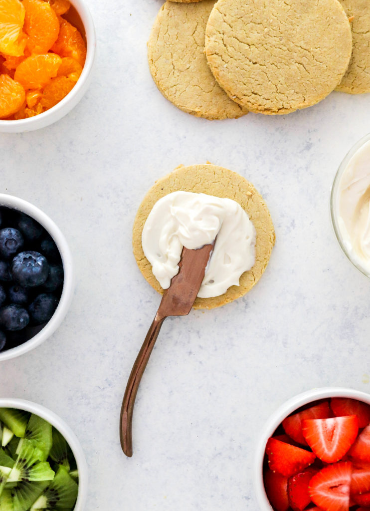 Round sugar cookie with a knife spreading frosting on it with more cookies behind it with bowls of fruit around it
