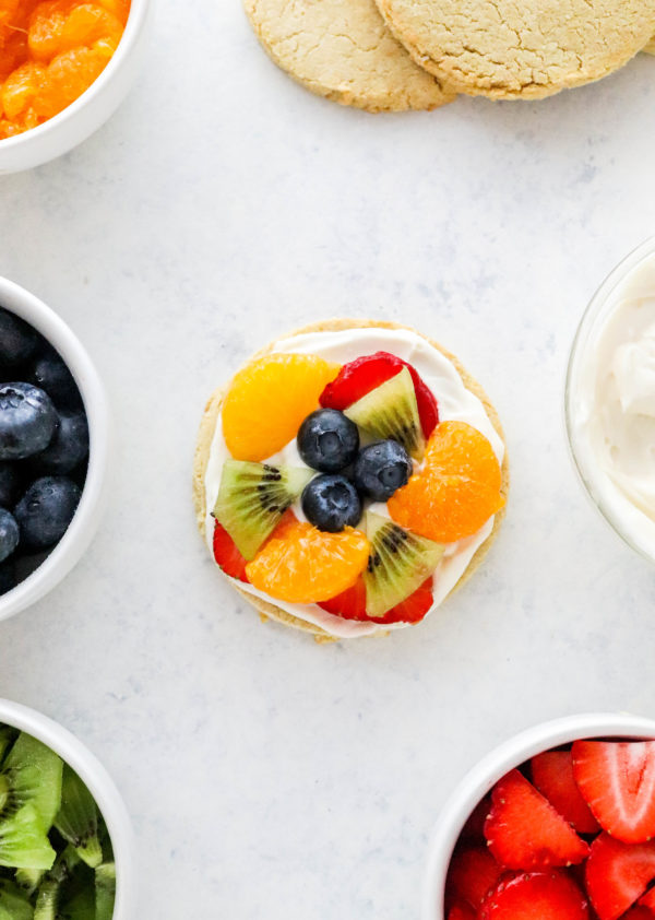 Fruit pizza cookie on a white surface with small bowls of fruit and a bowl of white frosting around it
