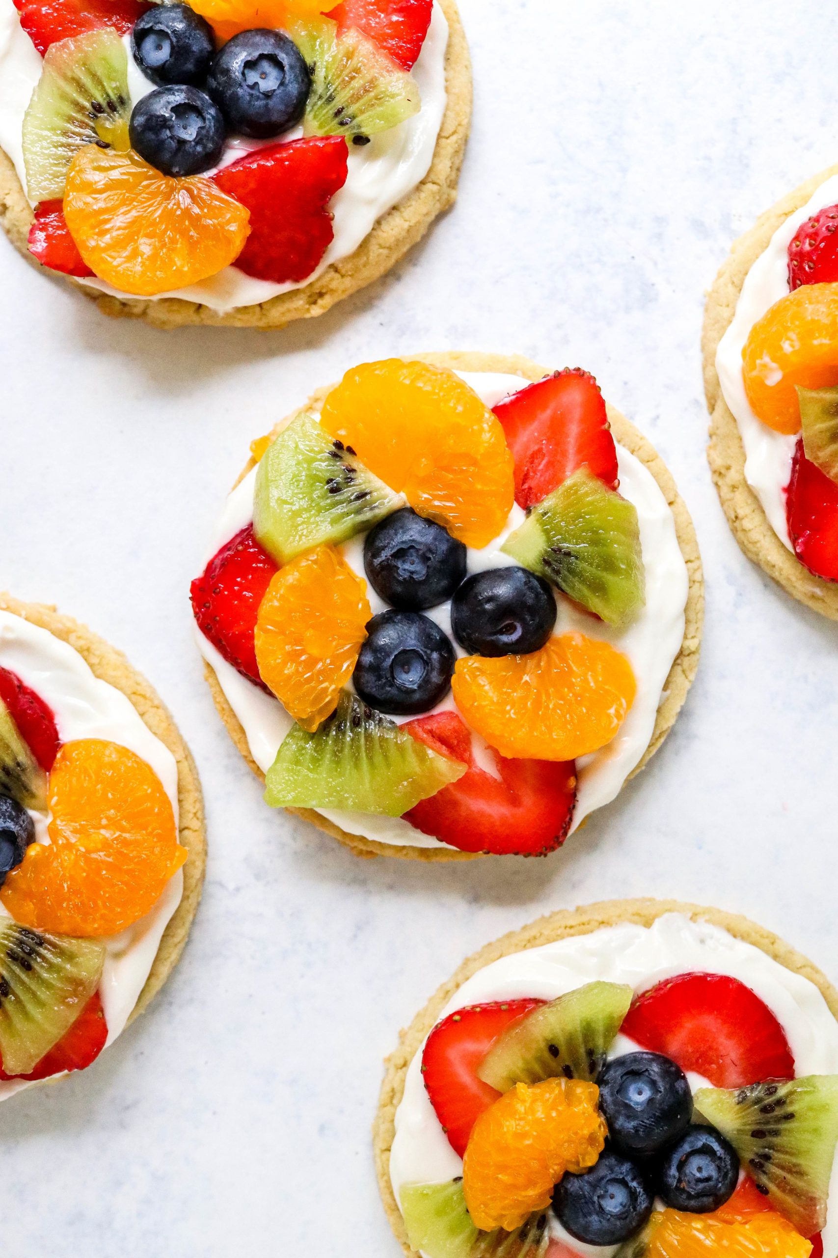 Fruit pizza cookie in the centre of a white surface with more fruit pizza cookies around it.