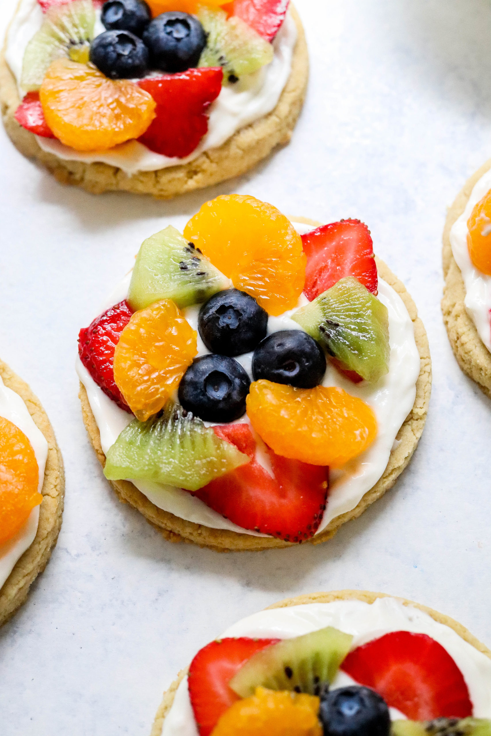 Close up shot of a fruit pizza cookie with more cookies around it on a white and blue surface.