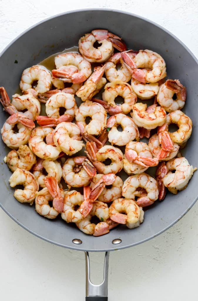 Grey pan filled with cooked shrimp on a white surface