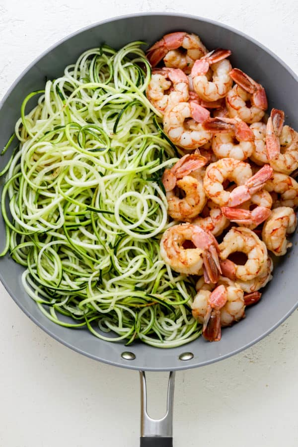 round grey pan with zucchini noodles on one half of the pan and cooked shrimp on the other half of the pan on a white surface