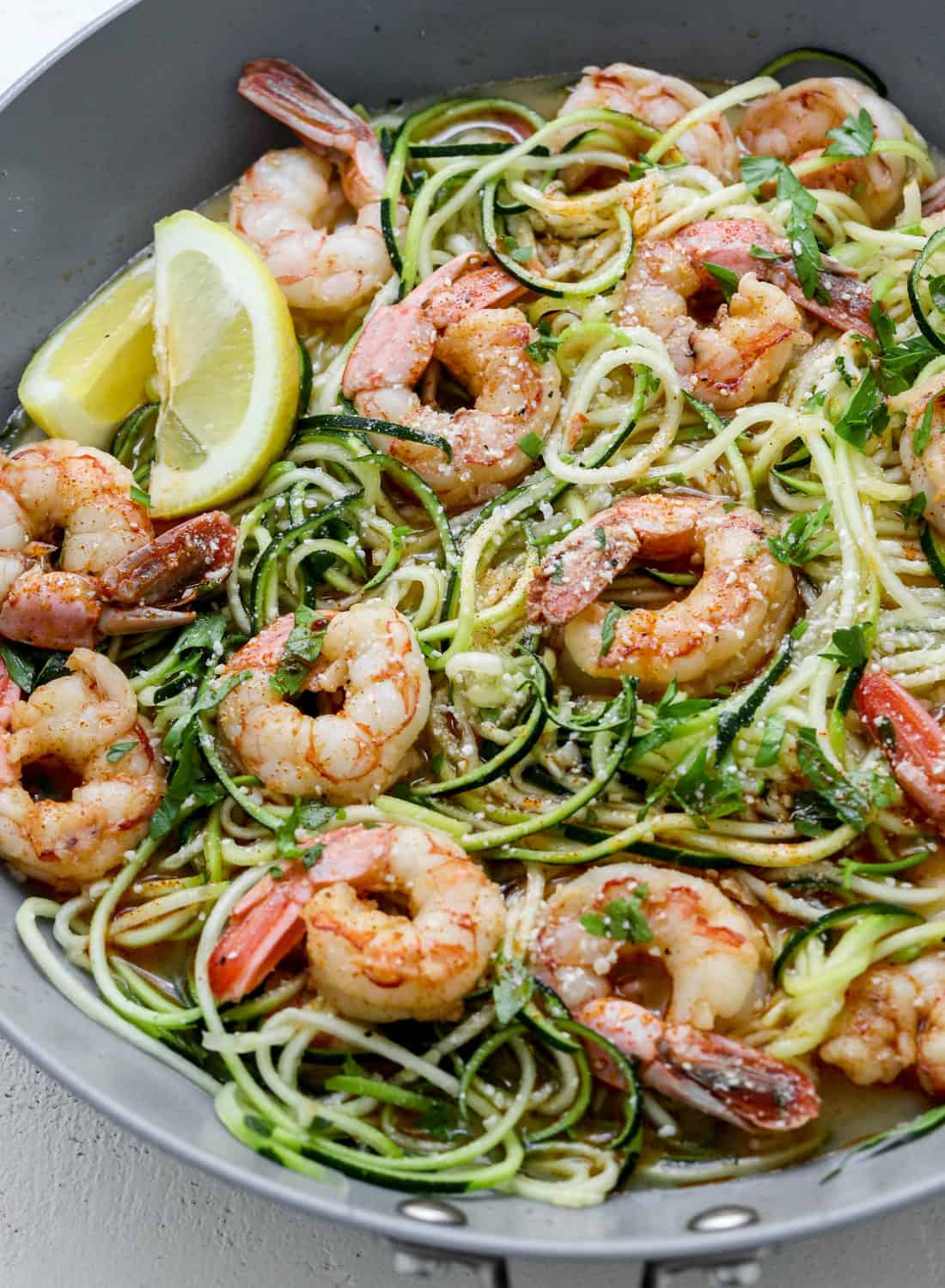 Round grey pan with cooked healthy shrimp scampi with zucchini noodles with lime wedges on the side of the pan and parmesan on top of the shrimp.