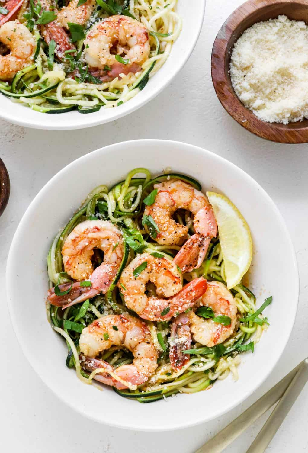 Round white bowl of shrimp scampi with zucchini noodles with another bowl of it behind it and gold plated silverware in front of it on a white table.