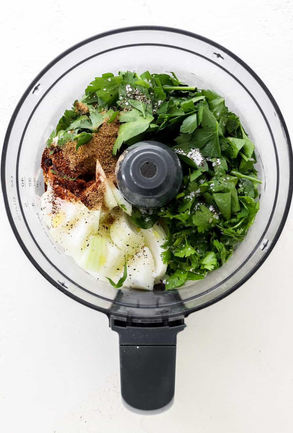 Bowl of a food processor filled with chopped onion and fresh herbs