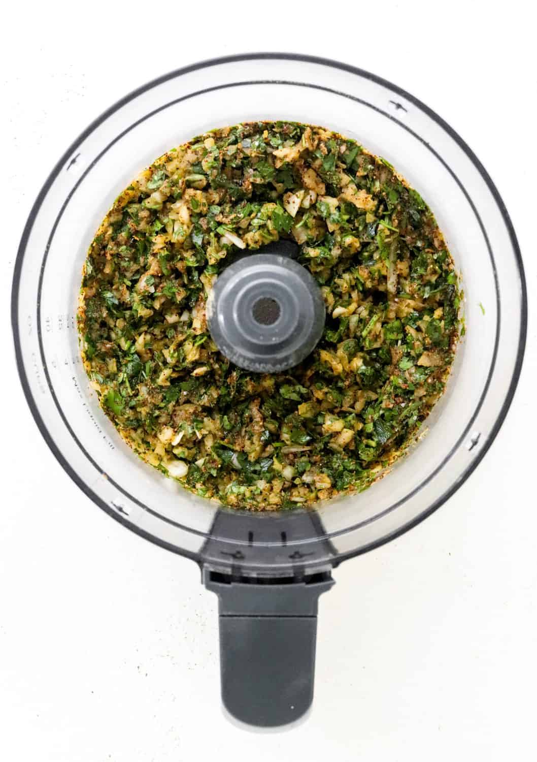 Bowl of a food processor filled with an herby chickpeas mixture