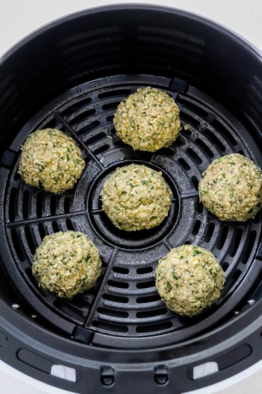 Rolled balls of falafel in an air fryer basket