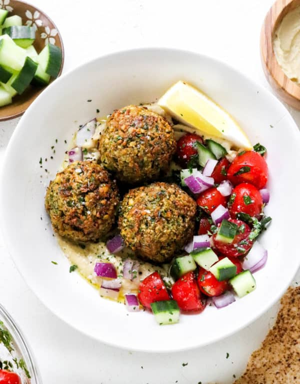 Golden brown falafel on top of hummus with chopped fresh cucumber and tomatoes with a bowl of chopped cucumber and a bowl of hummus behind it