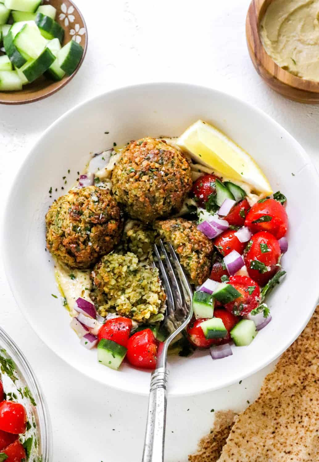 Round white bowl with crispy falafel in it on top of hummus, chopped tomatoes, cucumber and onion with a fork cutting into one of the falafel.  With more chopped cucumber and hummus in bowls behind it.