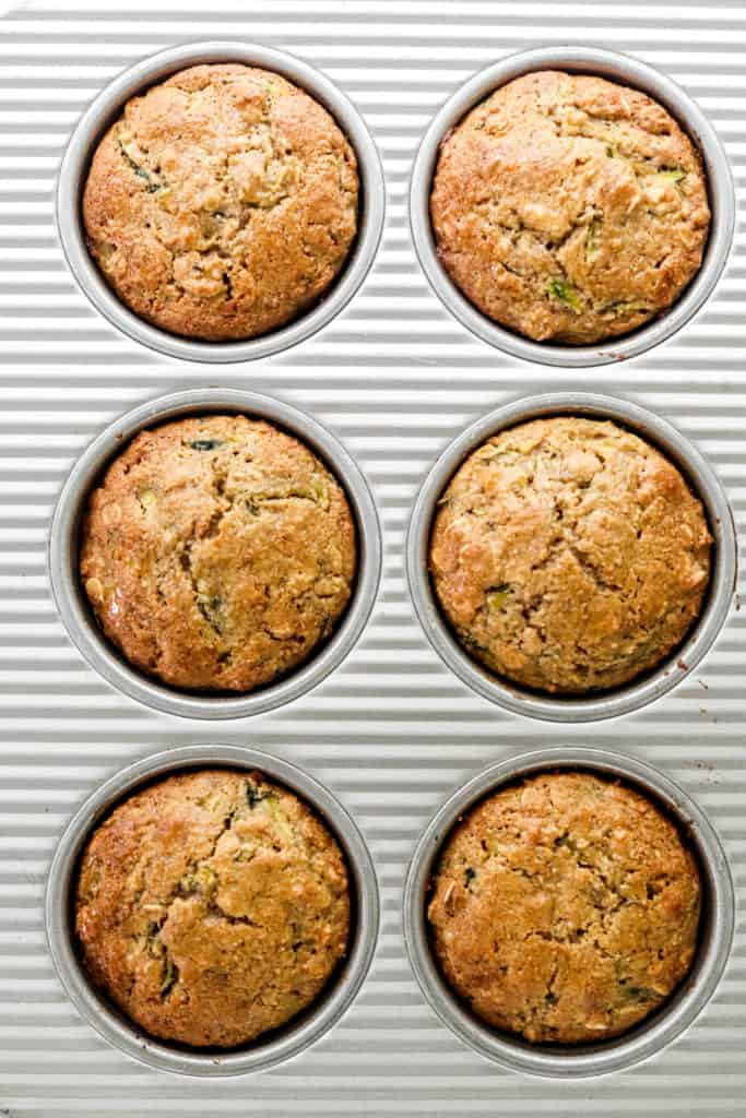 6 baked healthy zucchini muffins in a metal muffin pan
