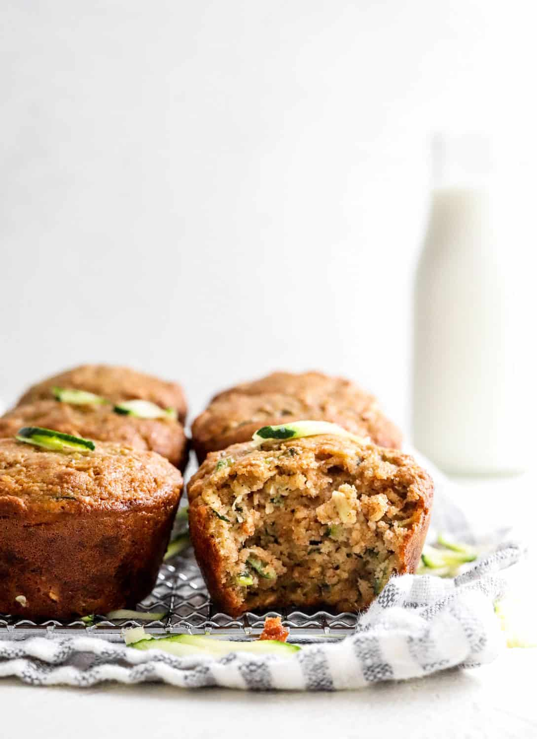 Two rows of healthy zucchini muffins with a bite taken out of one on a wire rack with a striped linen under it with a bottle of milk behind the muffins.