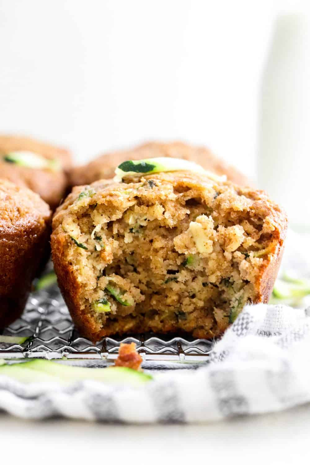 Close up of a zucchini muffin with a bite taken out of it with more muffins next to it sitting on top of a wire rack with a striped kitchen towel underneath it.