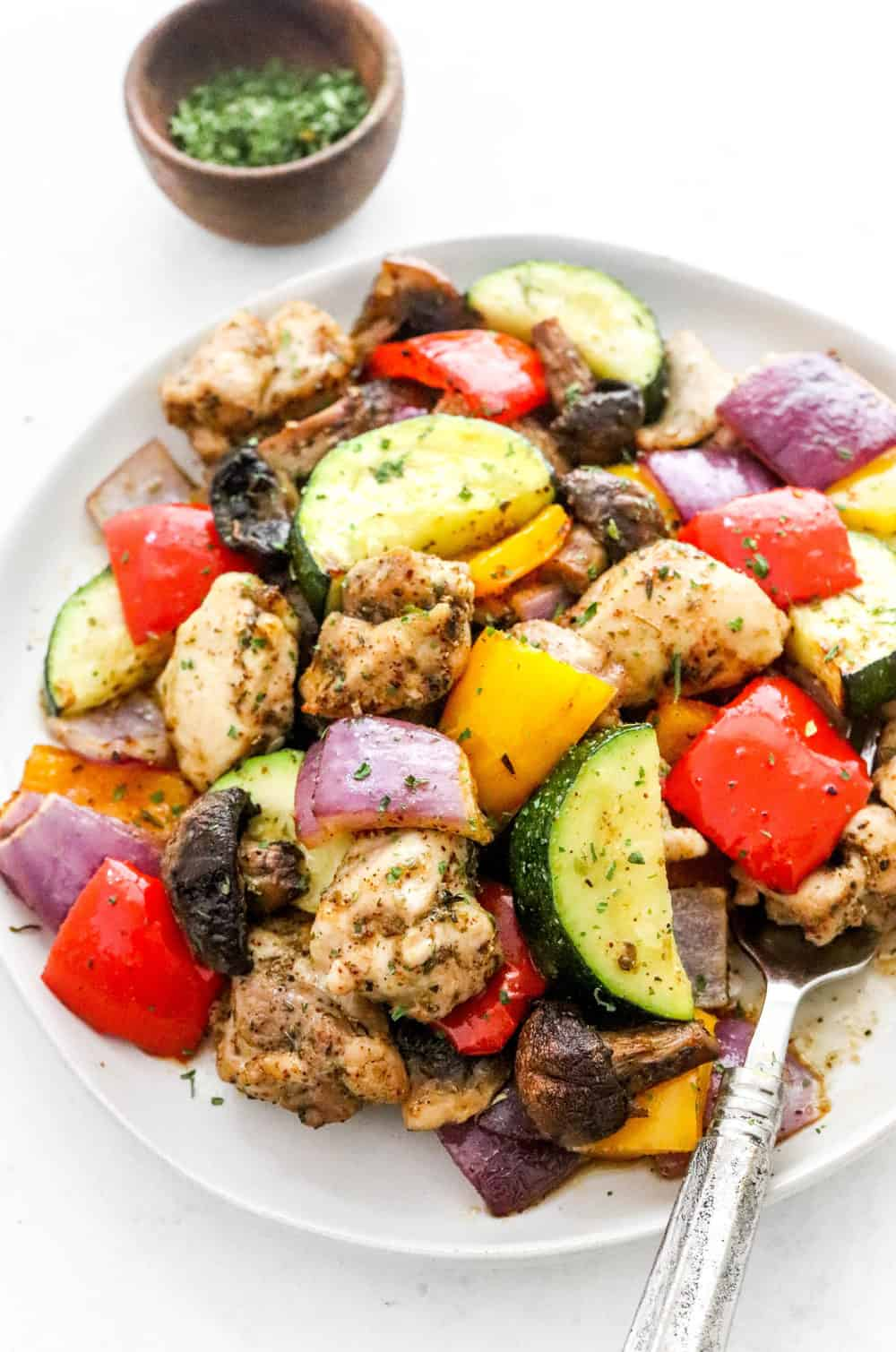 Grey round plate with sliced cooked zucchini, peppers, onions and chicken on it with a fork on the plate on a white surface.