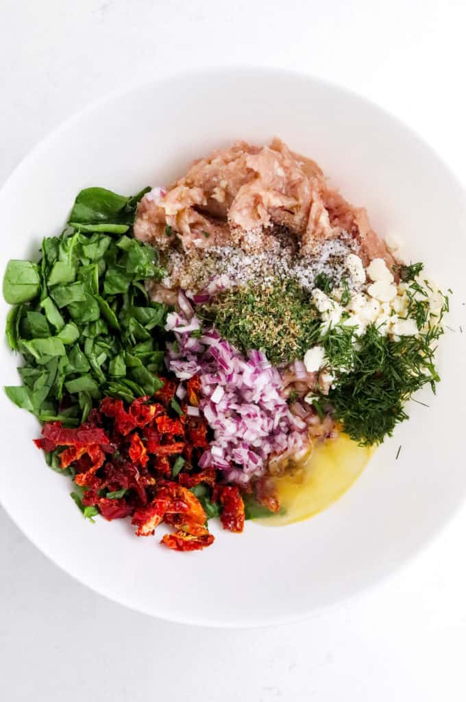 ground chicken, spinach, diced red onion, tomatoes , herbs and spices in a round white mixing bowl