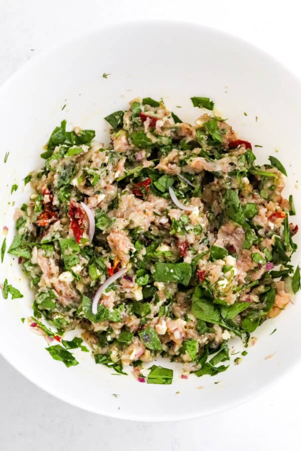Green and red ground chicken mixture in a large white mixing bowl