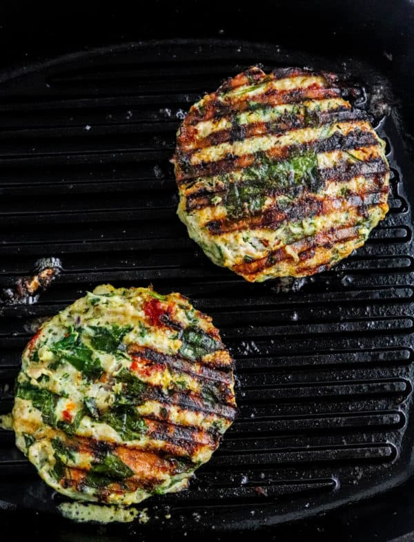 Two chicken burgers being grilled on a black grill pan