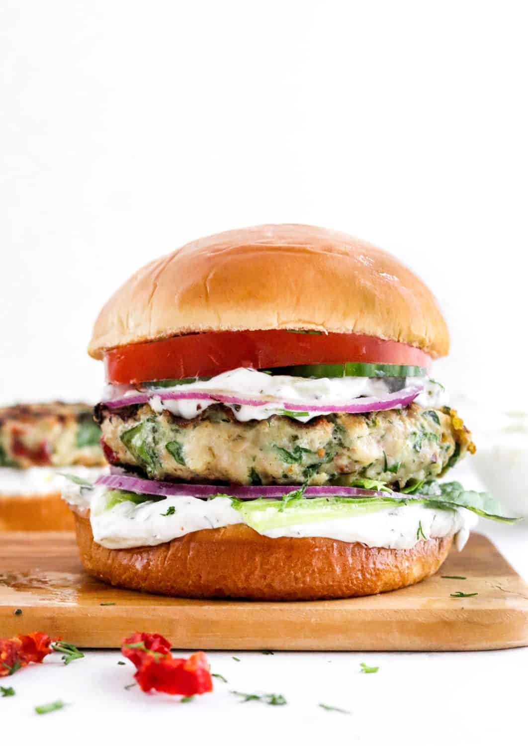 Chicken burger between a bun with white sauce on it and sliced tomato and red onion on a brown cutting board.