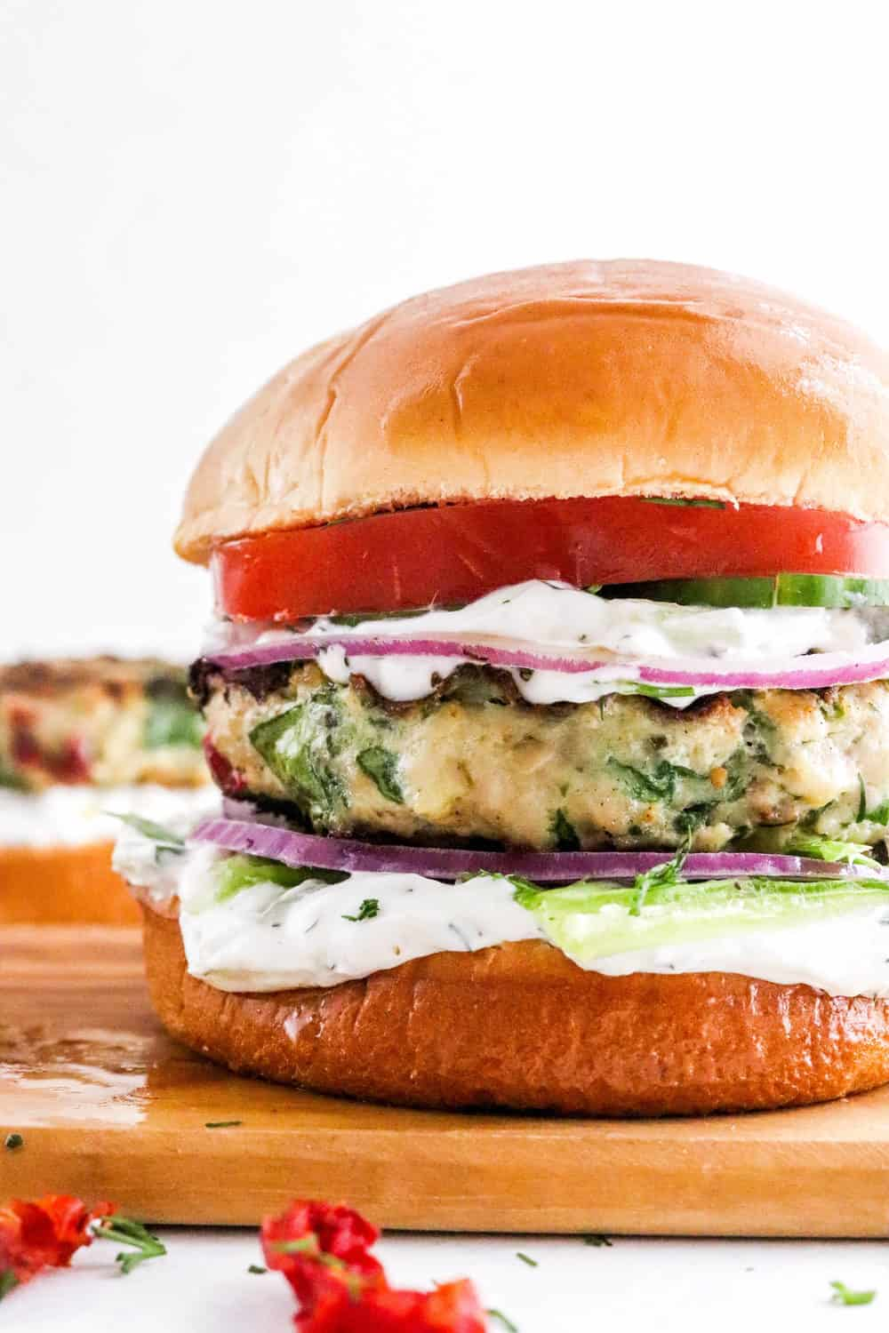Close up of chicken burger on a bun with white taziki sauce and sliced tomato, cucumber and purple onion on it in a brown board.