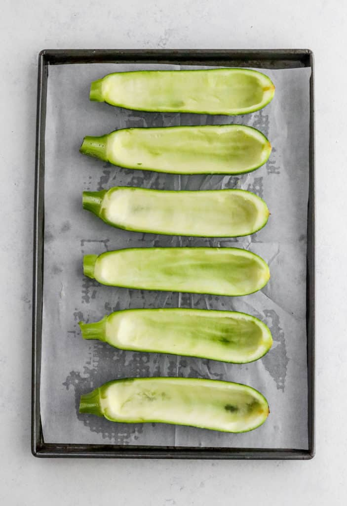 Sliced, hollowed out zucchini on white parchment paper on a grey baking sheet