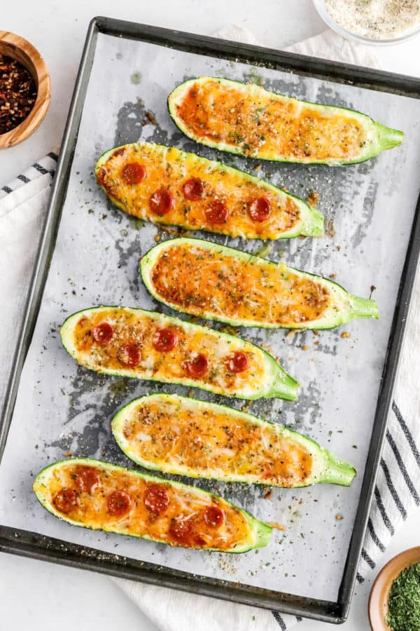 Cooked zucchini pizza in a baking sheet on parchment paper with a bowl if red pepper flakes behind it on top of a stripped towel